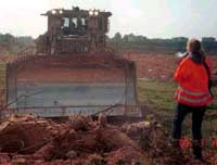 Rachel Corrie, holding a megaphone, confronts an Israeli bulldozer driver attempting to demolish a P